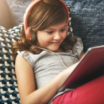Shot of a little girl wearing headphones while using a digital tablet at home